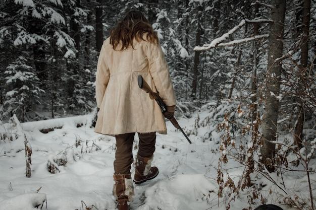 Jäger im winter vintage kleidung geht durch wald mit pistole
