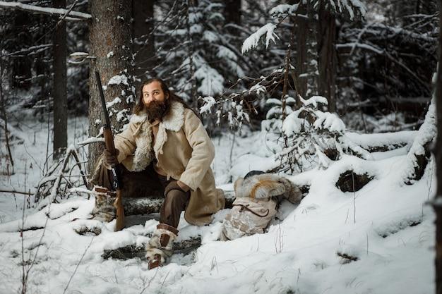 Jäger im winter vintage kleidung mit bart im wald mit pistole