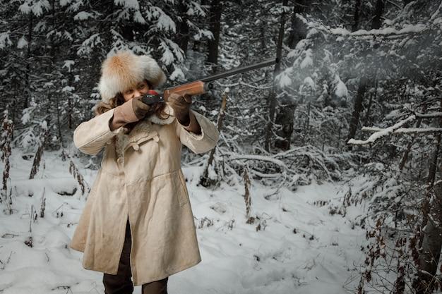 Jäger im winter vintage kleidung schießt pistole im wald