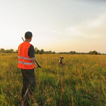 Jäger in der herbstjagdsaison mit seinem jagdhund auf sonnenuntergang.