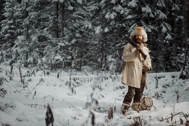 Jäger in vintage-kleidung mit pistole schleicht durch den wald