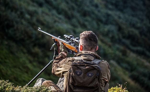 Jäger mann. jagdzeit. mann mit einer waffe. nahaufnahme. jäger mit jagdgewehr und jagdform zum jagen. jäger zielt. shooter, der im ziel anvisiert. der mann ist auf der jagd. jagdgewehr jagen.