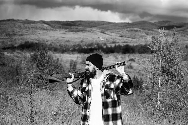 Jäger mit schrotflinte auf der jagd. autunm jagd. geschlossene und offene jagdsaison. jagdausrüstung und