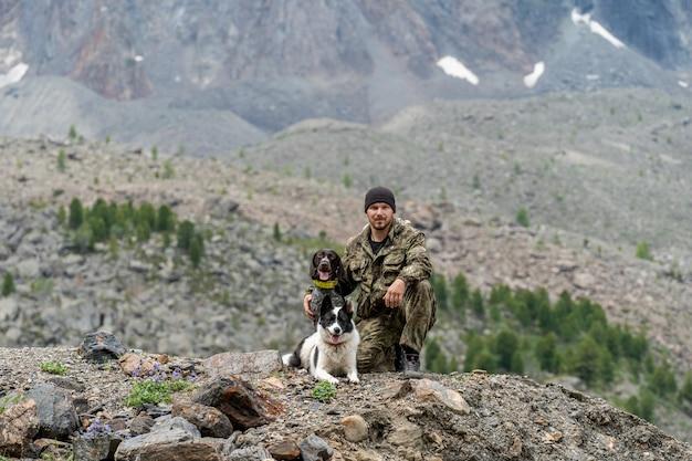 Jäger mit zwei hunden, die vor dem hintergrund eines berges sitzen