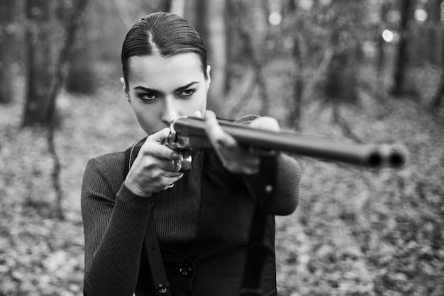 Jägerfrau mit schrotflinte auf der jagd. jagd im wald. porträt der frau hunter. geschlossen und offen