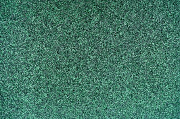 Jägergrüne farbe schindeldach textur hintergrund. dachmaterial. dichte der rauen dunkelgrünen granulatoberfläche des schindeldachtexturhintergrunds. schindeldach aus asphalt, kunststofffaser.