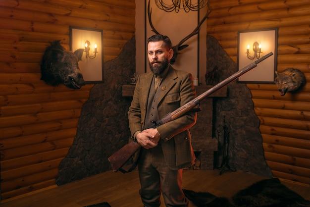 Jägerherr in traditioneller jagdkleidung mit alter waffe gegen kamin.