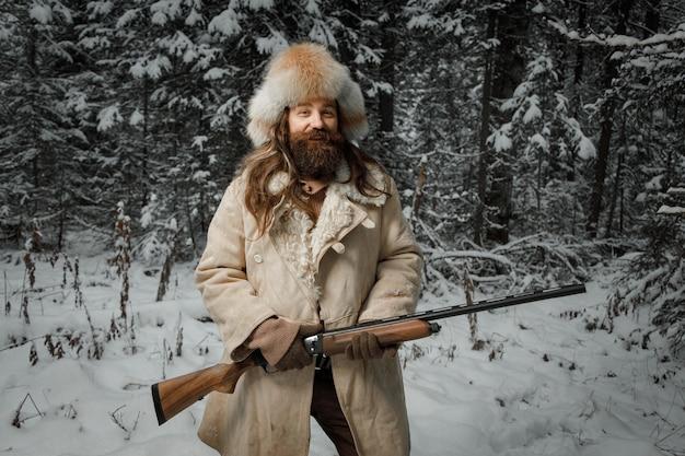 Jägermann im winter warme weinlesekleidung mit pistole im winterwald