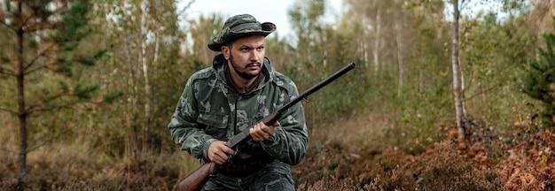 Jägermann in der tarnung mit einer gewehr während der jagd