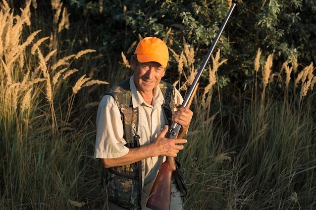 Jägermann in tarnung mit einer waffe während der jagd auf der suche nach wildvögeln oder wild. jagdsaison im herbst.
