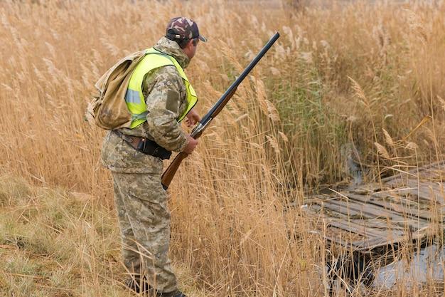 Jägermann in tarnung mit einer waffe während der jagd auf der suche nach wildvögeln oder wild
