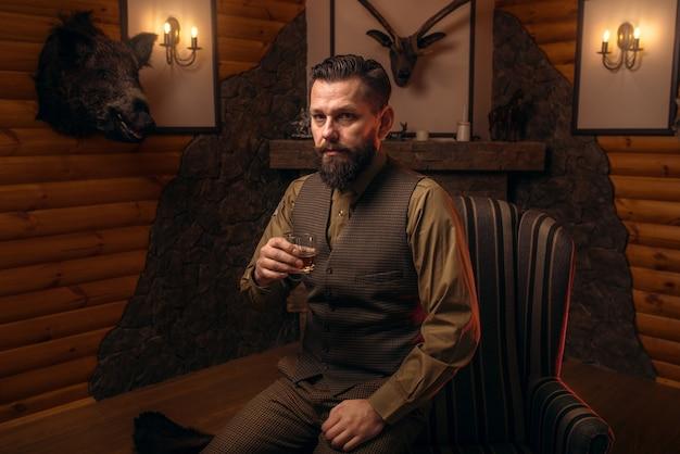 Jägermann trinkt alkohol nach erfolgreicher jagd
