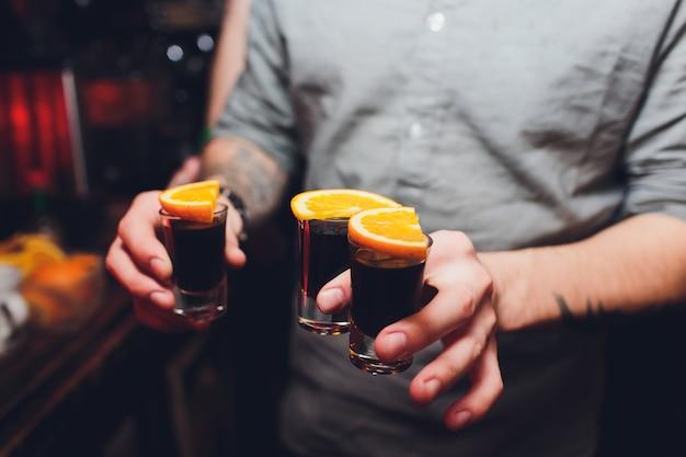 Jägermeister schießt cocktails mit orangefarbenem handmann.