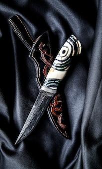 Jägermesser mit holzgriff auf dunkler oberfläche