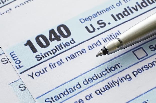 Jährliche steuerberichterstattung. steuerformular auf dem tisch. jahresabschluss zur unterschrift.