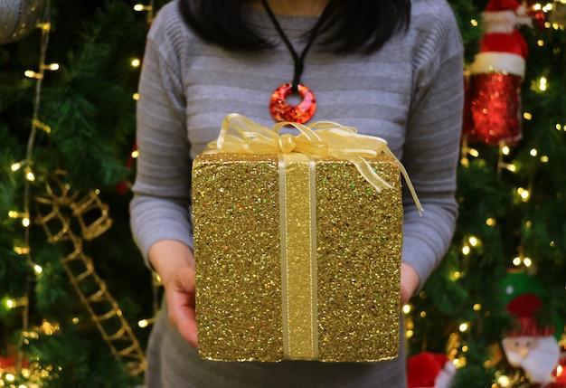 Jahreszeit des gebens eine frau, die goldfunkelnquadrat-formgeschenkbox in ihren händen hält