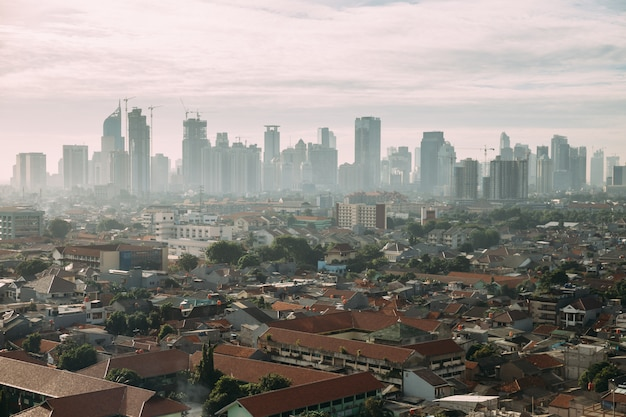 Jakarta-stadtbild mit hochhaus, wolkenkratzern und lokalen dachgebäuden mit rotem ziegeldach und nebel.