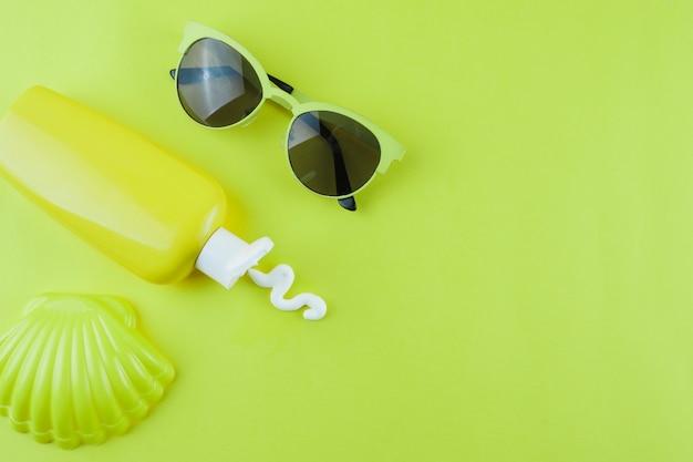 Jakobsmuschel aus kunststoff; sonnencreme und sonnenbrille auf grünem hintergrund