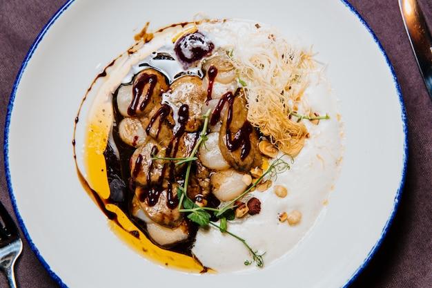 Jakobsmuschel-ceviche und foie gras mit haselnuss, servierfertig.