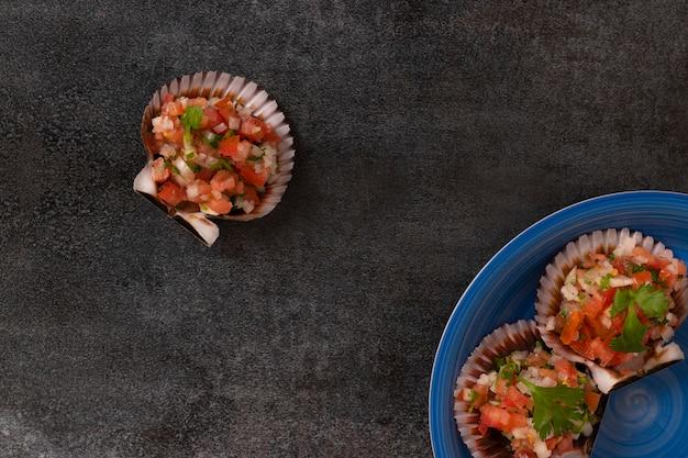 Jakobsmuscheln auf der schale mit tomaten und zwiebeln serviert