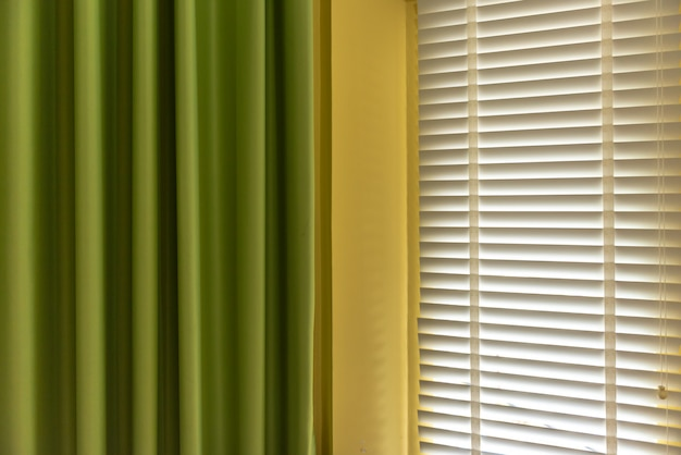 Jalousien am fenster oder jalousiefenster und grüner vorhang, jalousiefenster-dekorationskonzept.