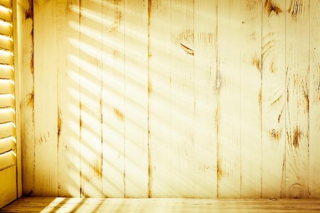 Jalousien sonnenlicht an der schäbigen holzwand