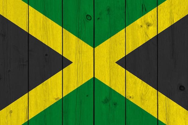 Jamaika-flagge gemalt auf alter hölzerner planke