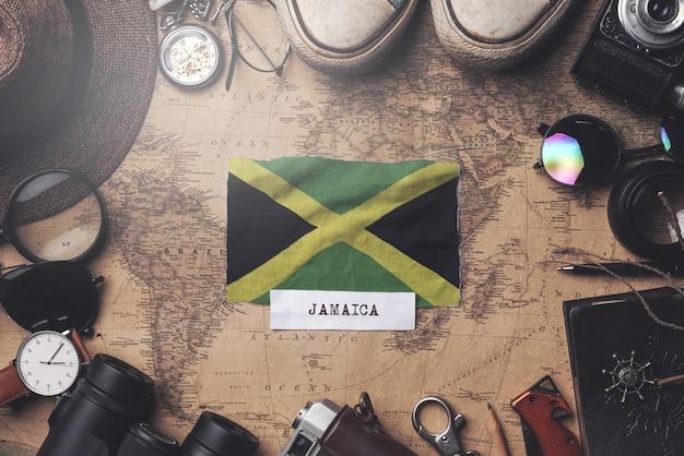 Jamaika-flagge zwischen dem zubehör des reisenden auf alter weinlese-karte. obenliegender schuss