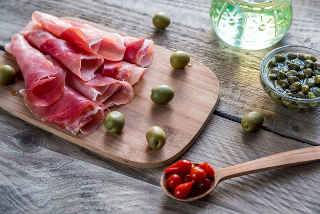 Jamon mit kapern und oliven auf dem holzbrett