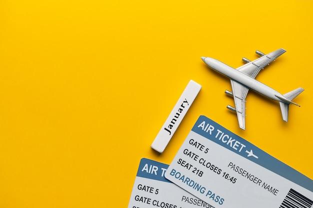 Januar urlaubskonzept mit flugzeug und tickets auf gelbem hintergrund mit kopierraum und draufsicht.