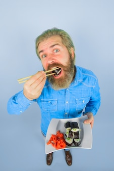 Japan sushi lieferung japanisches essen meeresfrüchte bärtiger mann mit teller sushirolle eingelegter ingwer teller