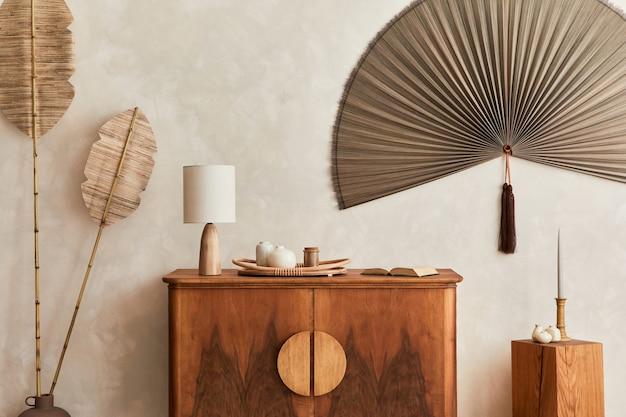 Japandi-konzept des wohnzimmerinnenraums mit design-holz-tischlampe tropisches getrocknetes blatt in vasenwürfeldekoration japanischer ventilator und eleganten persönlichen accessoires in der wohnkultur