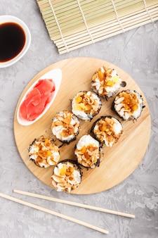 Japaner maki sushirollen mit sahne käse auf hölzernem brett auf grauem konkretem hintergrund. ansicht von oben.