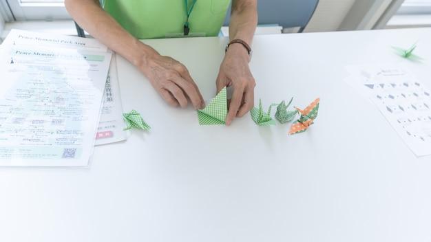 Japanerin, die zeigt, wie man origami-kraniche faltet, hiroshima, japan