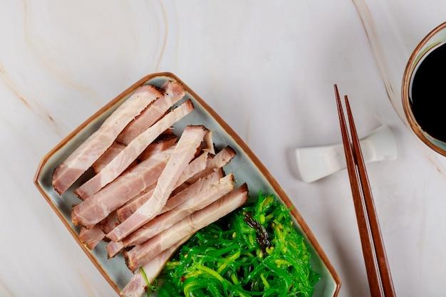 Japanische art schneidet fleisch mit meerespflanze, soße und essstäbchen