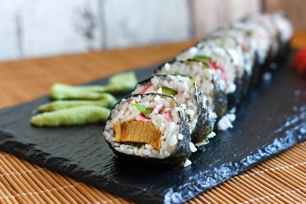 Japanische brötchen mit gurke, krabben und omelett auf einer schwarzen tafel mit wasabi und ingwer