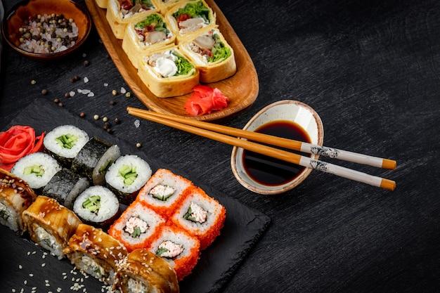 Japanische brötchen, sojasauce und sticks auf schwarzem schieferbrett und brötchen mit hühnchen und frischkäse auf dem tisch.