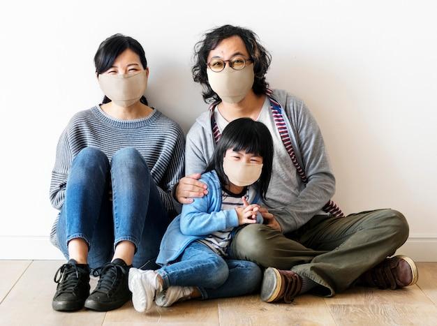Japanische familie, die gesichtsmasken innerhalb des hauses trägt