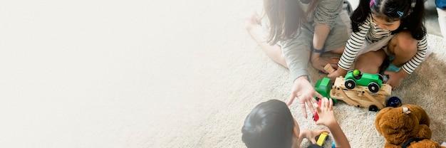 Japanische familie, die mit spielzeug auf dem bodengestaltungsraumbanner spielt