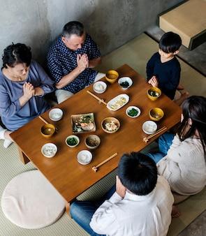 Japanische familie, die zusammen mit glück diniert
