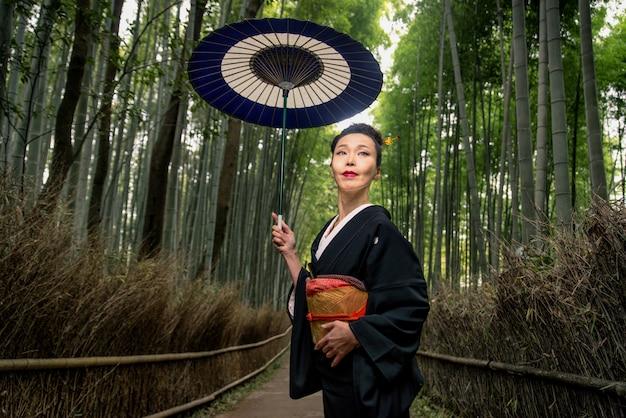 Japanische frau mit kimono im arashiyama-bambuswald