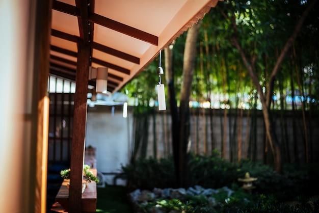 Japanische glocke, die am dach mit sonnenschein am japan-garten hängt.