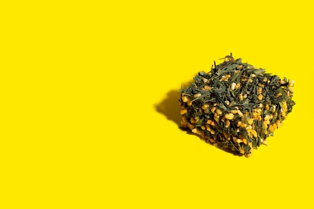 Japanische grüntee-genmaicha-teeblätter mit gebratenem naturreis in würfelform auf einem hellen