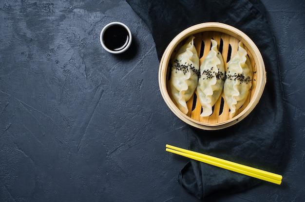 Japanische gyoza in einem traditionellen dampfer, gelbe stäbchen