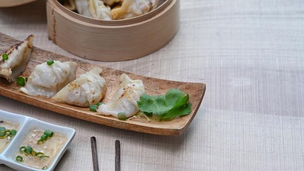 Japanische gyozas und knödel snack in rechteckigen holzteller und essstäbchen auf holztisch