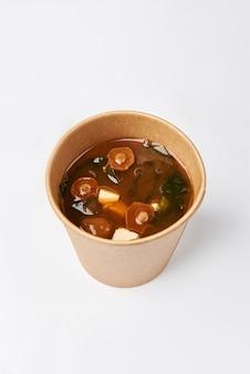 Japanische küche - miso-suppe mit seetang, pilzen und tofu-käse und lachs