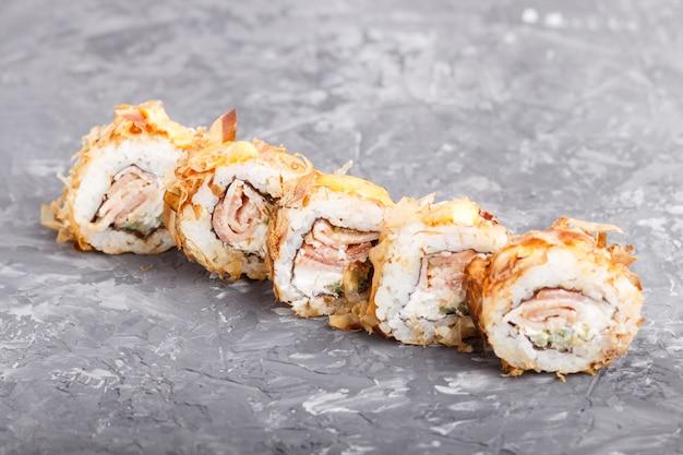 Japanische maki-sushi-rollen mit thunfisch, gurke, käse auf schwarzer betonoberfläche. seitenansicht.