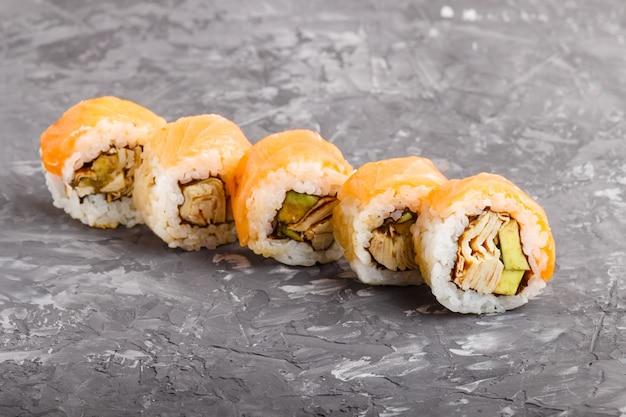 Japanische maki-sushirollen mit lachs, avocado und omelett. seitenansicht.