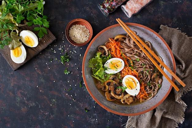 Japanische miso ramen nudeln mit eiern, karotten und pilzen. suppe leckeres essen.