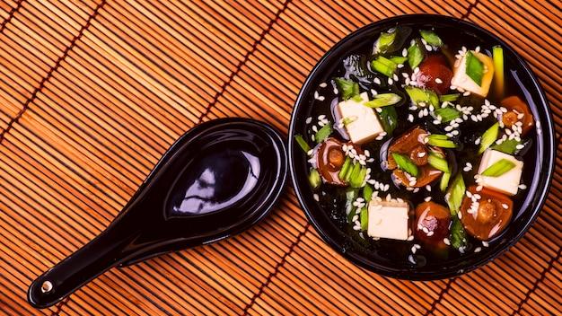 Japanische misosuppe in einer schwarzen schüssel auf bambusserviette.